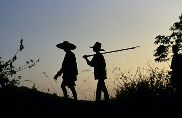 Two farmers (in silhouette) returning home at sunset.