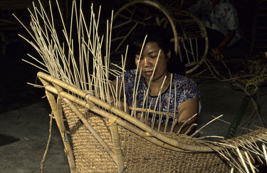 A woman making a wicker armchair with dried water hyacinth stems.