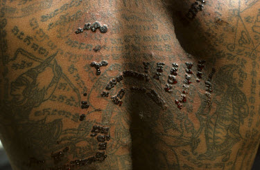 New tattoos are drawn amongst old ones on a man's back. It is said that yantras (geometrical diagrams) tattoos are good luck and can offer invulnerability if done by a tattooist possessing a magic pow...
