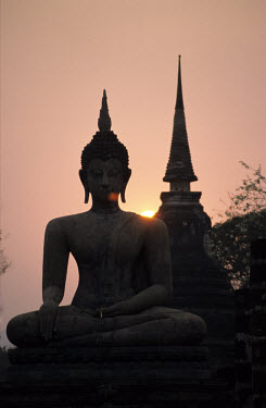 A sitting Buddha sculpture in the Bhumisparsa (Touching the Earth) posture at Wat Mahathat temple (built c. 13th century) in the historical park of Sukhothai.