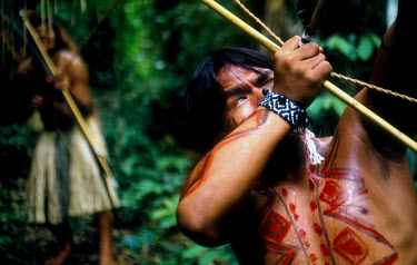 A father and son from an indigenous community hunting for wild birds with bows and arrows in the Amazon region.