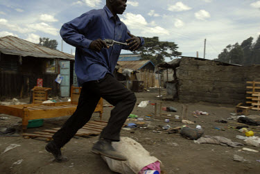 A plain clothed police officer, with a pistol in his hand, chases down a looter on the outskirts of Nakuru. Ethnic violence sparked last December following protests against disputed election results,...