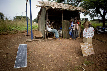 In Bangassou, four children talk to a man in a wooden hut who is selling batteries and solar power to charge mobile phones.