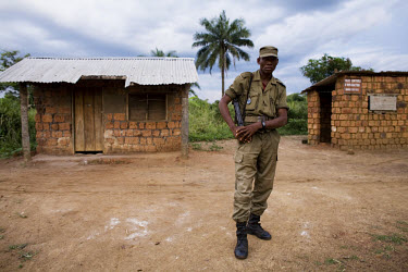 A military Gendarme carrying a gun stands outside a tin-roofed hut at a border crossing point .