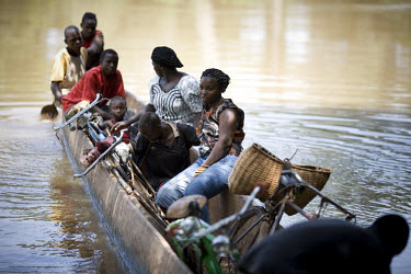 Men, women and children cross the river Mbari near Bangassou with their bicycles and other belongings in a large wooden canoe.
