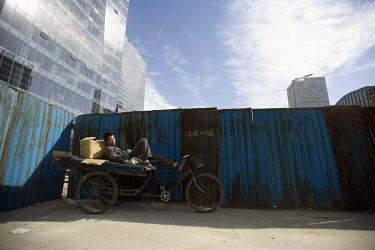 A migrant worker sleeps next to the construction site of a modern building in Eastern Beijing.