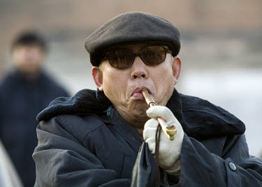 An elderly man smokes a pipe in Beijing. China has 350 million smokers, whose numbers are growing by more than 3 million a year.