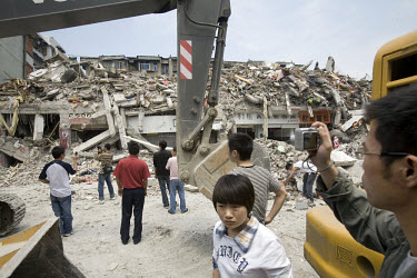 A survivor from the earthquake looks away in distress as others view the devastation caused by the recent Sichuan earthquake of 12/05/2008, which measured 8.0 on the Richter scale.