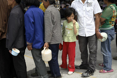 A child is among those waiting in line for food in a temporary shelter at the Jiuzhou Stadium in Mianyang. On the 12/05/2008 an earthquake measuring 8.0 on the Richter scale hit the province of Sichua...