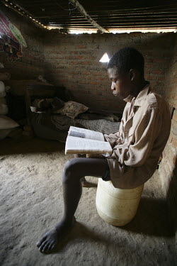 A schoolboy reads in his home.