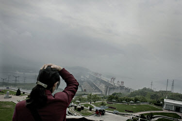 A woman looks out over the Three Gorges Dam and the Yangtze river.