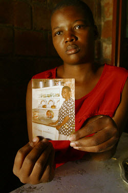 Girl holding a photograph of her mother, who died from AIDS.