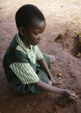 A child writes in the mud of her outdoor classroom.