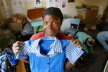 Women making clothes hold up a school uniform they have just made for one of their children.