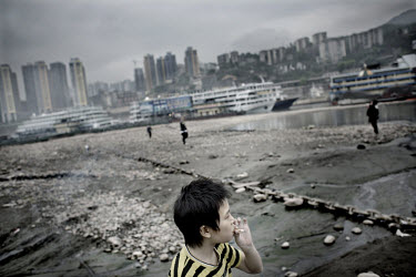 A child smokes whilst playing on the banks of the Yangtze river.