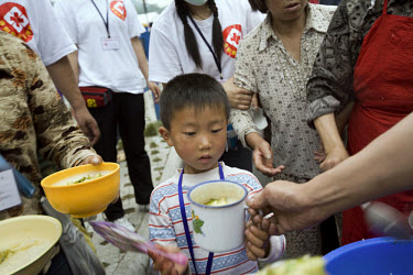 Volunteers help serve food in Nanhe stadium after the recent Sichuan earthquake of 12/05/2008, which measured 8.0 on the Richter scale. As the rescue effort goes on the death toll continues to rise, w...