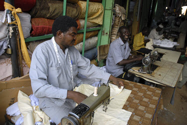 Men work at sewing machines at a tailors in Omdurman.