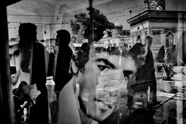 The faces of 'martyrs' killed during the Iran-Iraq war (1980-88) are reflected as a funeral takes place in the cemetery in the main square in Qom.