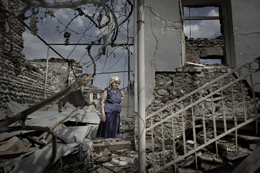 A woman stands amongst the bombed houses in the village of Tkviavi, between the South Ossetia border and Gori. After the Russian Army invaded the area, most of the inhabitants fled the village.