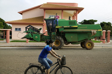 Mauricio Bernardini sits on a combine harvester outside his family's new home in Canarana. Like the majority of families in this part of town, the Bernardini family are Southern immigrants that were i...