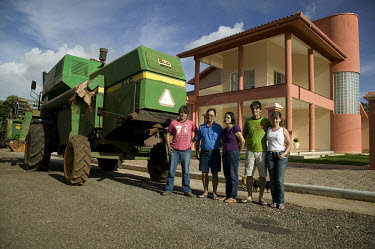 The Bernardini family stand beside their combine harvester in front of their new home in Canarana. Like the majority of families in this part of town, the Bernardini family are Southern immigrants tha...