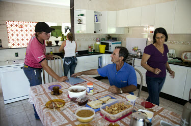 Olenir Bernardo Bernardini talks at the breakfast table with his son Mauricio about farm business in their new house in Canarana. Like the majority of families in this part of town, the Bernardini fam...