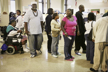 Black voters, one in a wheelchair, queue at the polling station in the Altgeld housing project in South Chicago on the day of the 2008 presidential election. The project is where Barack Obama first cu...