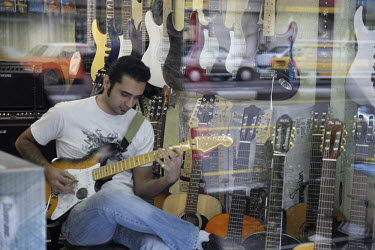 "Behnam, 23, is a musician and works in a shop selling guitars and other instruments. He was asked what his dreams are: ""My dream is to see rock concerts in the streets of Tehran."""