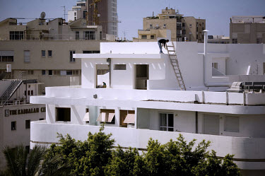 A man paints the roof of a Bauhaus building in Dizengoff Circus. 2009 is the city's centenary, and the Bauhaus inspired architecture of the city will be one of the focus points of the celebrations. In...