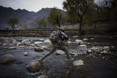 A US Army soldier from 3rd Platoon, Charlie Company, 1-26 Infantry crosses a river as he returns to base following a meeting with village elders.