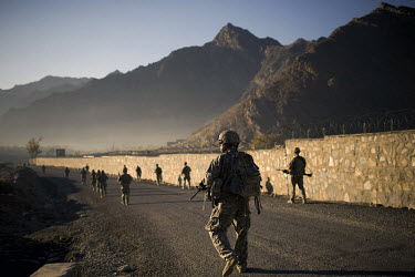 US Army soldiers from Charlie Company, 3rd Platoon patrol in Nanglam village in the Pech Valley. The unit was providing security for a local English school graduation ceremony in an effort to maintain...