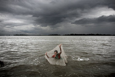 A woman fishes with a net off the island of Padma Pakur. The sea in the Bay of Bengal is rising, affecting the hundreds of thousands of villagers living on the low islands in the south. When Cyclone A...