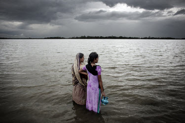Women look out over the rising sea water. The sea in the Bay of Bengal is rising, affecting the hundreds of thousands of villagers living on the low islands in the south. When Cyclone Aila hit Banglad...