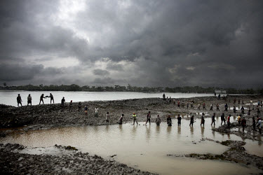Men form a human chain to carry mud up to the embankment. They are trying to build a new and stronger flood barrier after Cyclone Aila destroyed the old one. The sea in the Bay of Bengal is rising, af...