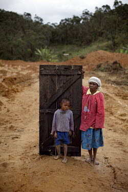 The Joajaoby family stand with their front door, the last remnant of their home after it was destroyed to make way for the 200km long pipeline leading from the Ambatovy Mine, owned by mining giant She...