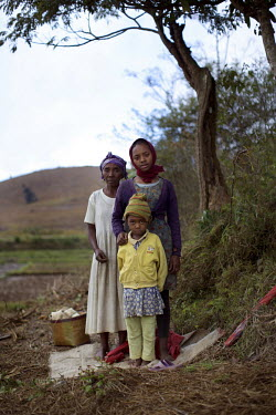 61 year old Razanadravad, from the village of Ambonierenana, stands with her grandchildren in her vegetable patch, 1 km from the Ambatovy mine entrance. The family have had dysentery due to drinking w...