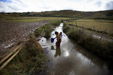 A woman collects polluted drinking water from a stream. Sherritt, one of the world's biggest mining companies, is constructing the world's largest nickel mine in Madagascar. At risk is one of the worl...