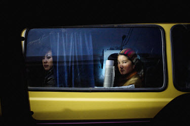 A woman looks out of the window of a minibus stuck in traffic in Osh.