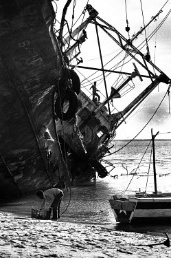A man fishes for shrimps next to a wreck of a big trawler in the old port of Beira on the Indian Ocean.