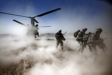 US Army soldiers from 1st Platoon, Baker Company, 3rd Battalion, 509th Infantry Airborne run off a helicopter during an air assault operation to search for an IED (improvised explosive device) factory...