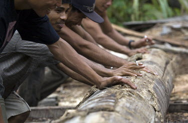 Workers roll a log in to a position to be cut into useable timber. The small saw mill receives logs from villagers, and the wood is then used for building houses and fences in the area.