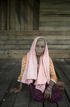 50 year old Rohanna sits outside her home in Kuala Cenaku village.