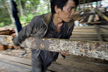 Bejang, a worker in a saw mill cuts a log into useable timber. The small saw mill receives logs from villagers, and the wood is then used for building houses and fences in the area.