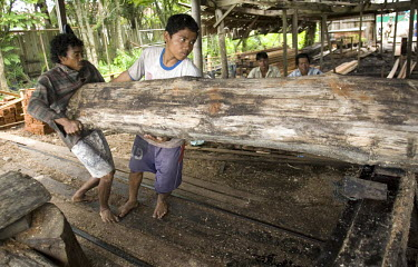 Workers in a saw mill cut a log into useable timber. The small saw mill receives logs from villagers, and the wood is then used for building houses and fences in the area.