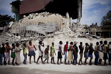 People queueing for distribution of food aid by the United Nations World Food Programme (UN WFP) in front of a building devastated by the earthquake.A 7.0 magnitude earthquake struck Haiti on 12/01/20...