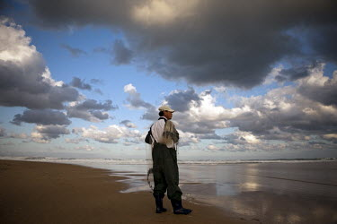 A fisherman looks out to sea on the coast at Hwajinpo.