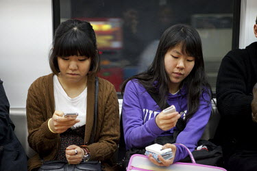 Young women with their mobile phones on the Seoul Metropolitan Subway.