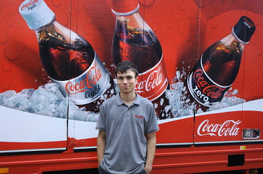 A Coca Cola delivery man standing next to his truck.