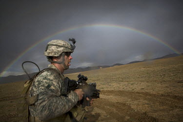 SGT Smith, US Army soldier from HQ Platoon, 1-503rd Infantry, 173rd Airborne runs for cover during a mortar attack near Jaghatu Combat Outpost, whilst a rainbow forms over the landscape.