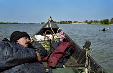 Hristu, a fisherman from Sfantu Gheorge, sleeps in the prow of his boat during the trip back home after a working day. The inhabitants of the Danube Delta live an isolated existance and make a living...